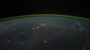 Australian bushfires seen from space. Note the green layer of atmosphere.